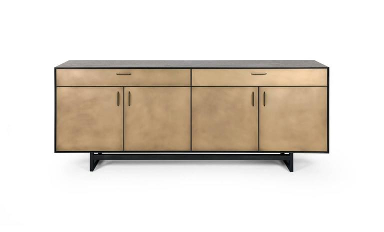 The Gotham credenza features clean lines that blend harmoniously with the beautiful mix of materials. A dark and dramatic oxidized walnut frame sits on a blackened steel base. Custom hand-sculpted blackened bronze pulls compliment the striking