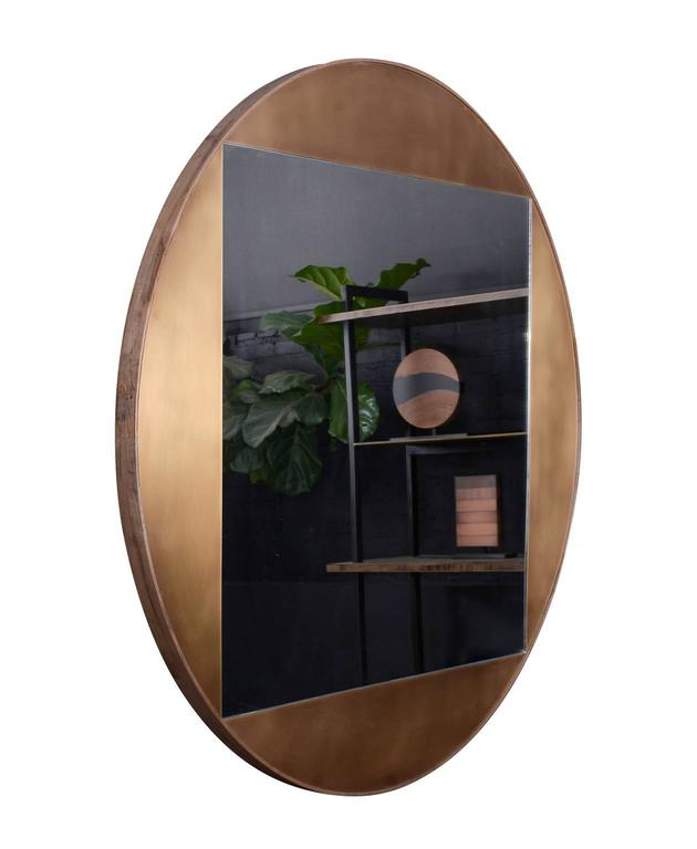 "Part of the elegant Gotham collection, the round mirror is composed of patinated bronze and oxidized ambrosia maple. The juxtaposition of shapes, both sharp and curved, lends balance and sophistication to this piece. One available in-stock 48""."