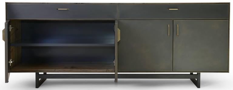 The Gotham credenza features clean lines that blend harmoniously with the beautiful mix of materials used in this collection. A delicate oxidized ambrosia maple frame sits on a blackened steel base with custom hand-sculpted bronze pulls on the