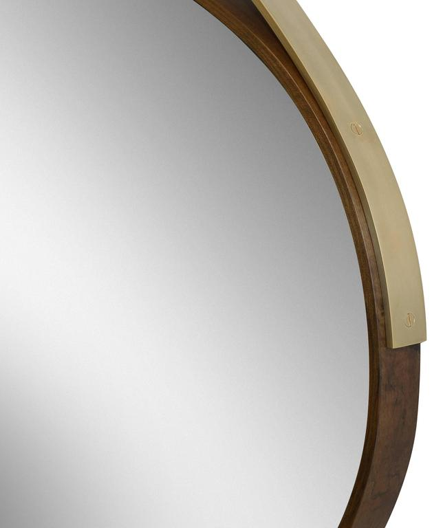 Part of the Gotham collection, the hand-crafted oval mirror features a bronze leaf inlay, a steam-bent oxidized Ambrosia maple frame, and a hand-turned bronze hanging structure, creating elegant curves in this modern design.
