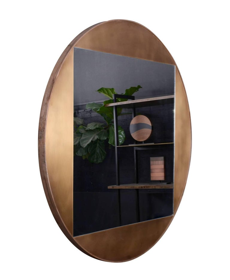Part of the elegant Gotham collection, the round mirror is composed of patinated bronze and oxidized ambrosia maple. The juxtaposition of shapes, both sharp and curved, lends balance and sophistication to this piece. Regular lead time 10-12