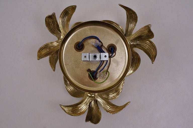 Brass flower light with three flowers in the style of Willy Daro by Massive, circa 1970s, Belgian.  Thoroughly cleaned, fully rewired, in full working order and ready to use.  This vintage ceiling light consists of a group of three gold tone brass