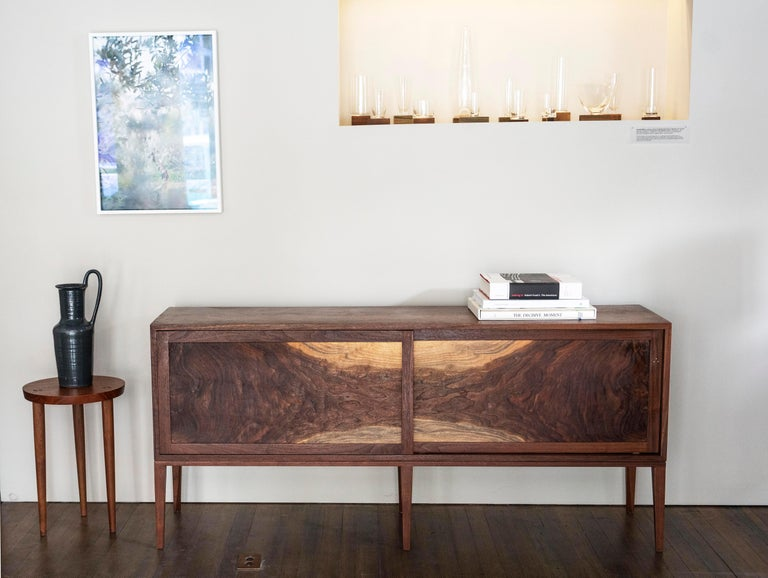 One of a kind. Two large sliding flat panel doors are the centerpiece for this Hudson Valley walnut cabinet; bookmatched flames radiating inwards are set off by two arches of pale sapwood. On the rear door, a bright but subtle moment of copper