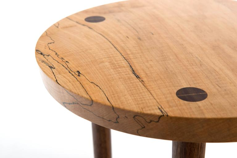 Edition of 15. This three-leg design centers around the through-cut joinery affixing the subtly beveled edge of the curly Maple top with the Black Walnut base. A graphic wedge of Maple in this joint bisects the circular face of each Walnut leg. To