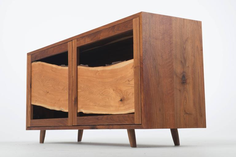 Juxtaposition. Curve with angles. Dark with light. Mass with void. Strength in design lies in the ability to create opposition and tension without becoming incongruous. The central panel in this sustainably made cabinet is a single sweeping board of