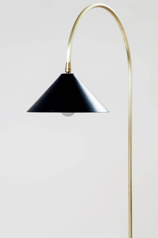 Inspired by the iconic Bishop's hook cast-iron street lamps that illuminate New York City's Williamsburg Bridge, this elegant floor lamp is comprised of a blackened-steel hand-spun shade, brushed-brass curved neck and ebony-stained ash wood