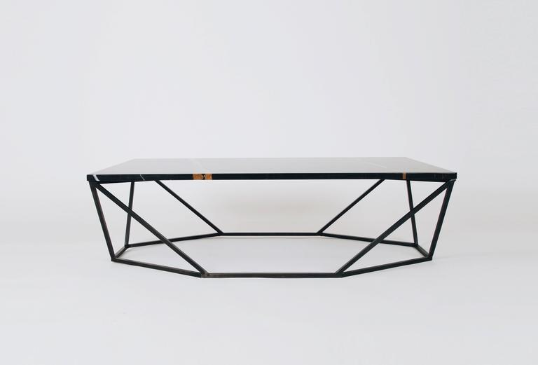 This rich finish combination for the dusk coffee table features a geometric blackened-steel base with a black nero Durata mable tabletop.