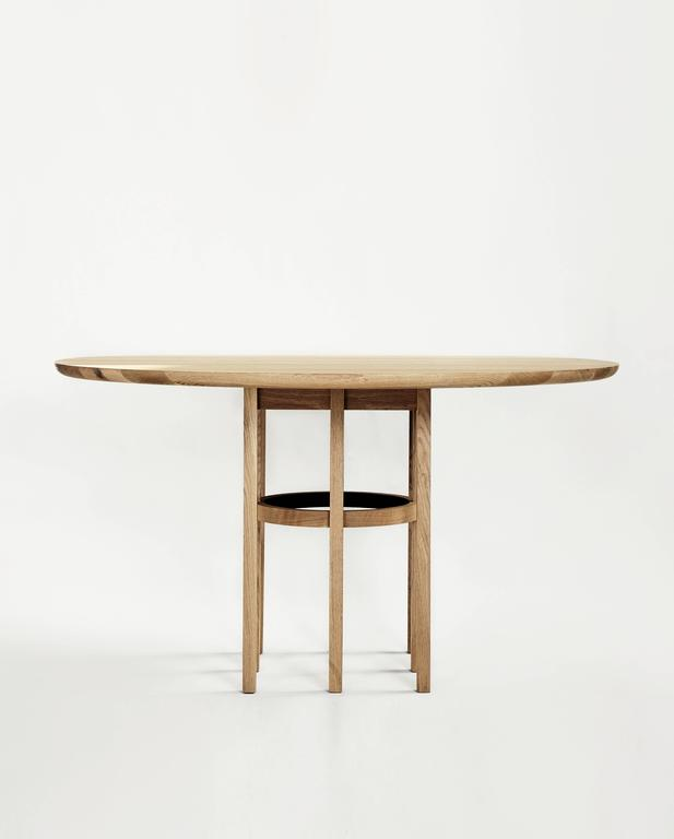 A leather-trimmed ring floats amidst eight identical legs, which support a circular tabletop. The Soren dining table completes the gesture of the Soren Chair's crescent-shaped backrest and acts as a centering point for surrounding chairs.