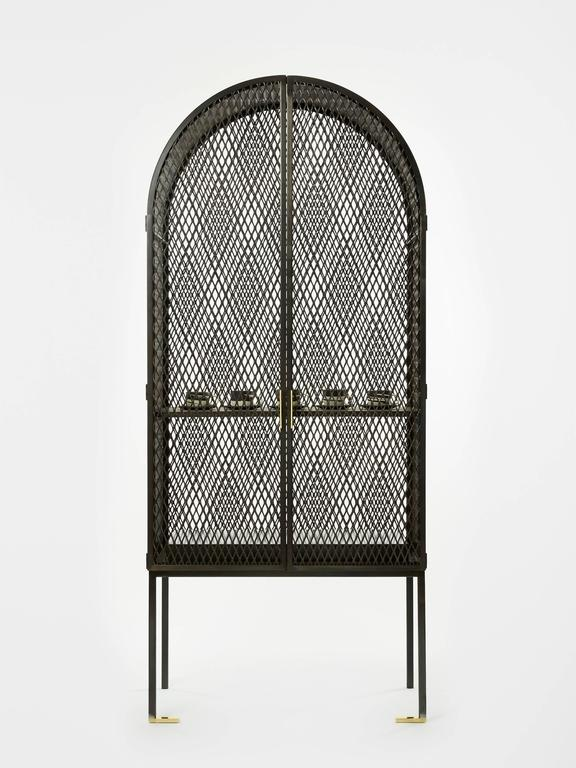 The Louise Cabinet is a study in simultaneity. It combines light with shadow, angles with arches, and blackened metal with glistening brass. 