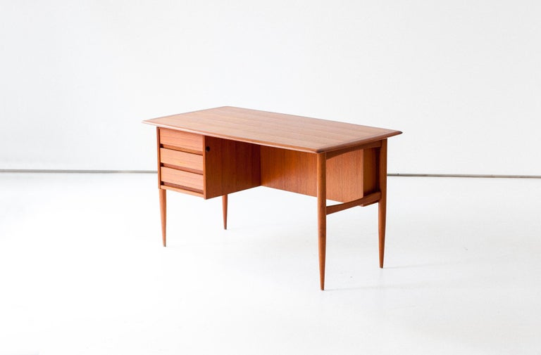 A scandinavian modern table with chest of drawers manufactured in Denmark in the 1950s It feature an open bookcase in the back and three drawers on the front This writing tables in made of teak wood Completely restored, there are only original