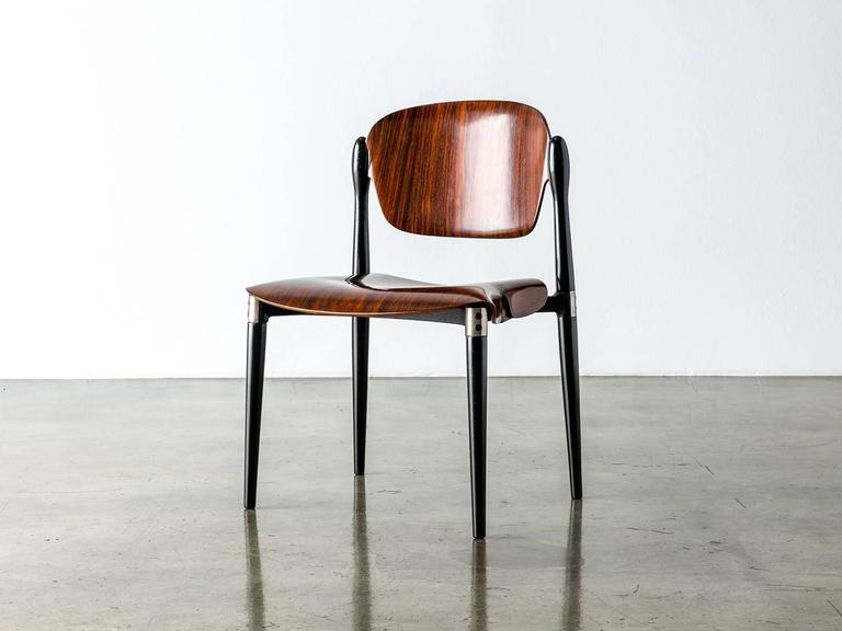 A compact and comfortable chair designed by Eugenio Gerli for Tecno in 1962 that suspends two molded rosewood panels to simple and elegant effect. Black lacquered legs are joined by a die-cast aluminum underside support and aluminum fittings. The