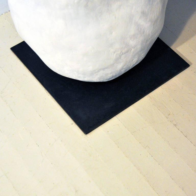 """Aiko tables are a study in contrast, each with a hand-cast organic, white concrete monolith sitting on a precise, blackened 14"""" steel square. Each cast form is made in a five-part casting process over several days, resulting in subtle"""