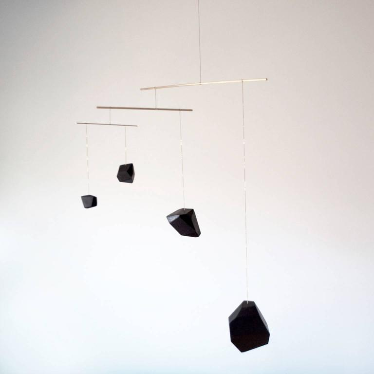 Large mobiles are made from solid walnut blocks which are hand-sculpted and slowly polished using vegetable soot ink until a hardened black surface approaches chatoyancy over the wood's grain. Four or more blocks are then arranged, silver soldered