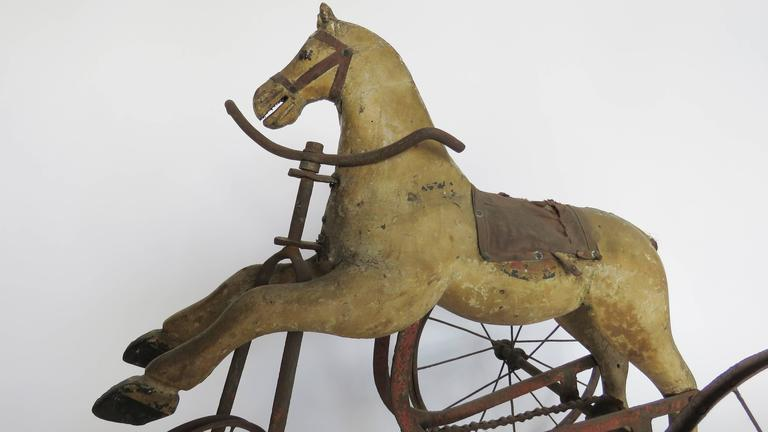 Wooden painted horse mounted on tricycle base.