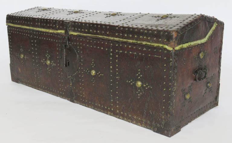 The hinged dome lid over a conforming rectangular case fitted with an iron lock plate and decorated overall with brass nailhead pattern in four quadrangles.
