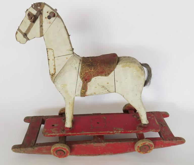 Painted horse with leather saddle mounted on four small wheels, can also be used on the wooden rocker.