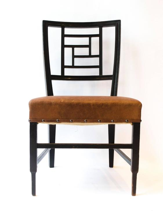 Edward William Godwin, an Anglo-Japanese ebonized side chair, probably made by William Watt. With a lattice back, a later overstuffed leather seat on square part-fluted supports. See Soros, Susan Weber 'The Secular Furniture of E.W. Godwin', p. 113,