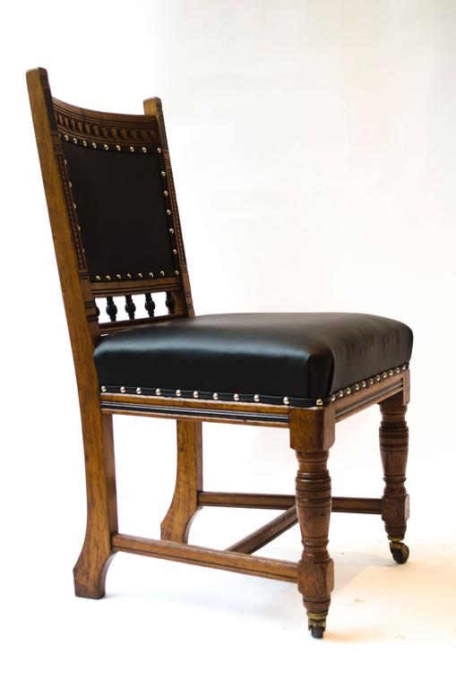Lambs of Manchester A Set of Four Aesthetic Movement Oak Dining Chairs with carved and part ebonised details, professionally reupholstered in a quality matt black leather.