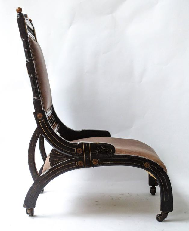 Richard Charles (1823-93), A rare Aesthetic Movement ebonized and parcel Gilt lounge chair, with a spindle gallery above and below the padded back rest, with arched shaped legs to each side from front to back also forming the seat and a smaller
