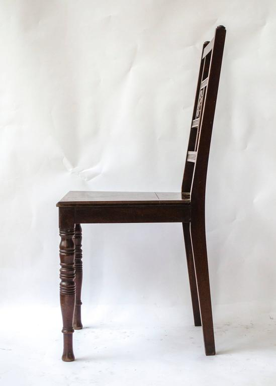 Attributed to Bruce Talbert and probably made by Gillows of Lancaster. Anglo-Japanese walnut side or hall chair with carved sunflower to the back on ring turned legs