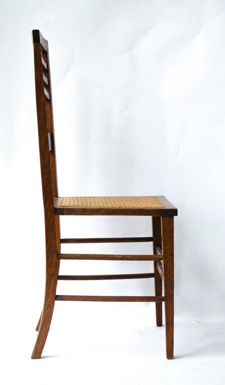 Shapland and Petter. An Arts and Crafts oak side chair with a pierced heart and chequered string inlays. New professionally laid cane seat.