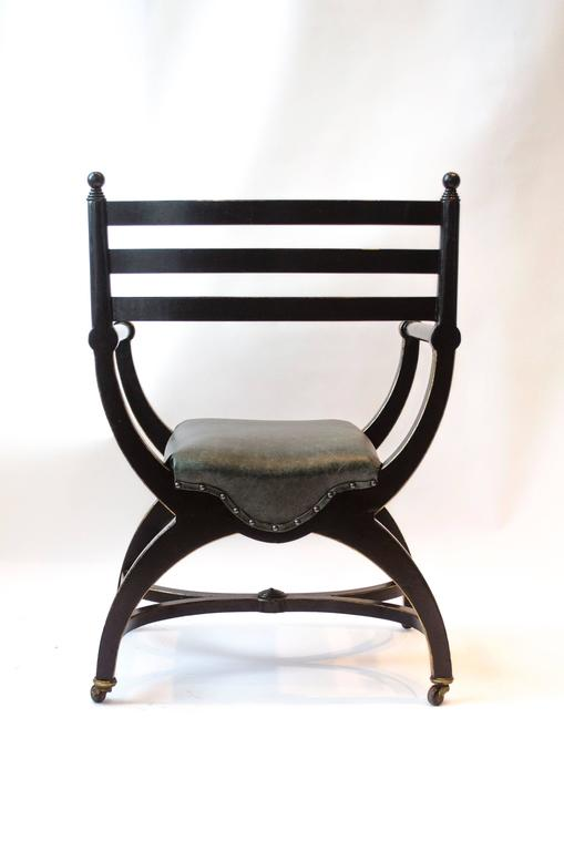 Richard Charles Aesthetic Movement Ebonised Elbow Chair with X Frame stretcher For Sale 1