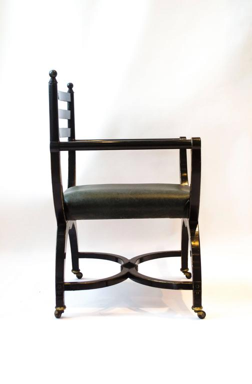 English Richard Charles Aesthetic Movement Ebonised Elbow Chair with X Frame stretcher For Sale