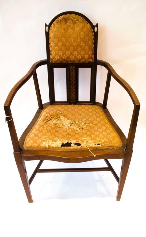 An armchair designed by George Montague Ellwood and made by J S Henry, with arched top and oval mother-of-pearl inlays just below the ears and sinuous arms with conforming seat details to the side and subtle curve to the front and extra