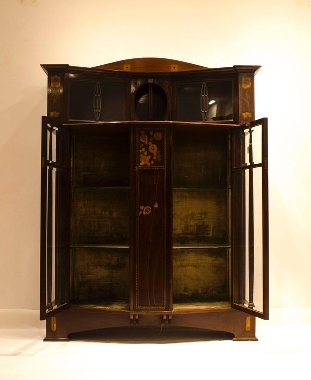 E. Goodall, Manchester, a mahogany, inlaid and leaded glass display cabinet, metal label. Known to have made furniture for Mackmurdo and the Century Guild. This piece made by Bath Cabinet Makers and retailed by Goodalls.