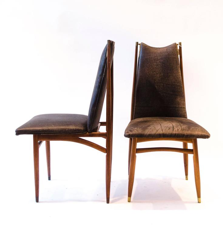 A stylish Mid Century Modern set of twelve dining chairs with sweeping upper stretchers and decorative brass fittings. I have had them professionally upholstered in a suede style leather.
