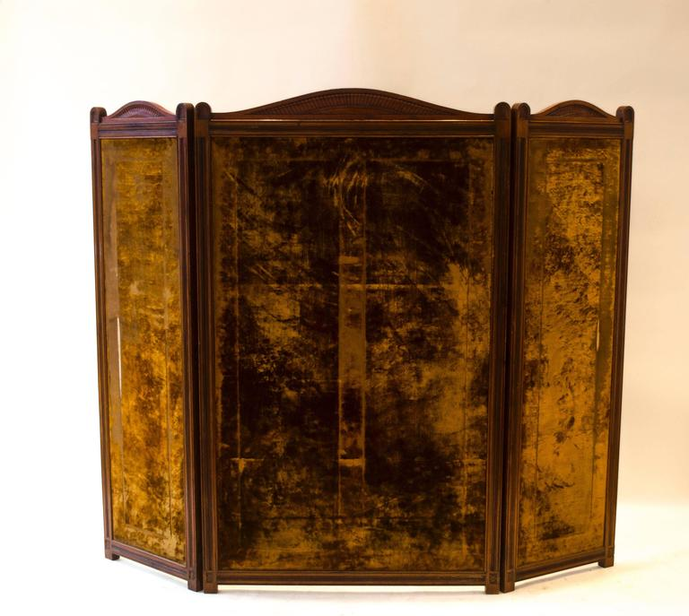 An Aesthetic Movement Walnut three-fold screen attributed to Bruce Talbert probably for Gillows with decorative carved detail's to the serpentine top, carved tramline detail around each panel and six carved florets to the bottom of each side,