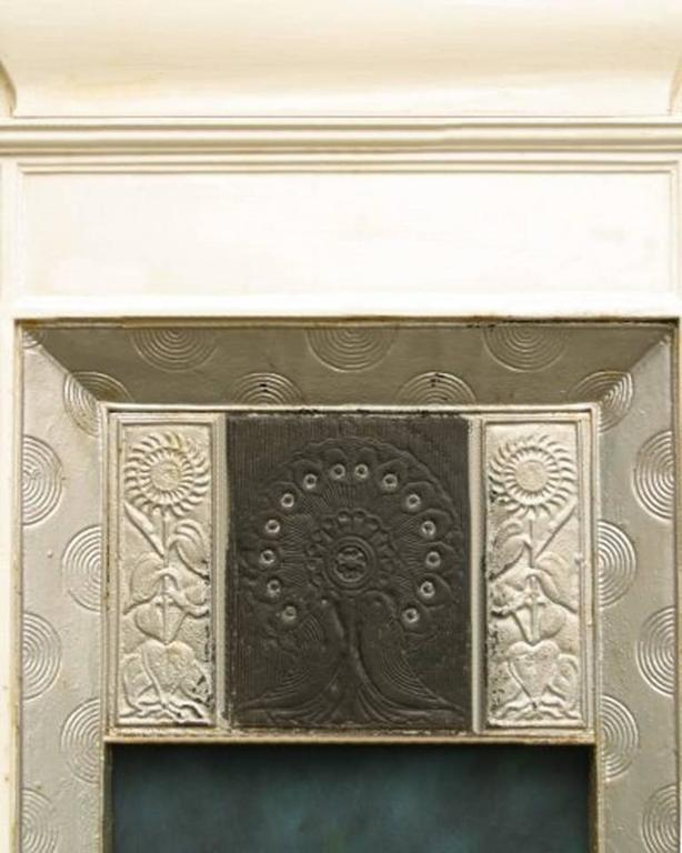 An Aesthetic Movement cast iron fireplace with peacock feathers to the centre and two love birds just below flanked by Sunflowers. Made by Thomas Elsley the design attributed to Thomas Jeckyll. We can have this stripped and polished or painted in