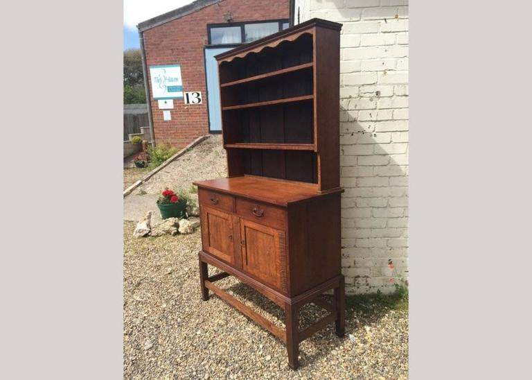 An excellent quality Arts and Crafts two-door oak dresser with a decorative shaped top, cascading upper shelves, and a sweeping arched apron on four square legs united by side stretchers.
