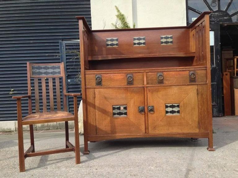 George Montague Ellwood, made by Bath Cabinet Makers,. An Arts and Crafts oak sideboard and eight matching dining chairs  The sideboard with elongated slatted sides with heart cut-outs and stylized ebony and pewter inlays to the back and to the