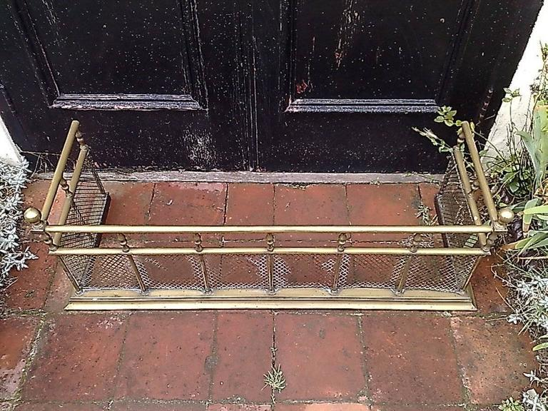 A good quality Aesthetic Movement brass fire fender with turned details and finials above, protective mesh to the lower part all stood on a solid brass plinth.