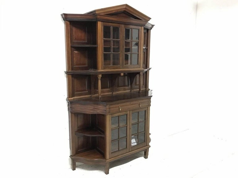 Morris & Co. A fine mahogany glazed breakfront bookcase designed by George Jack of exceptional quality typical to all Morris & Co furniture. With upper and lower central glazed sections both flanked by open semi-serpentine corner shelves with a
