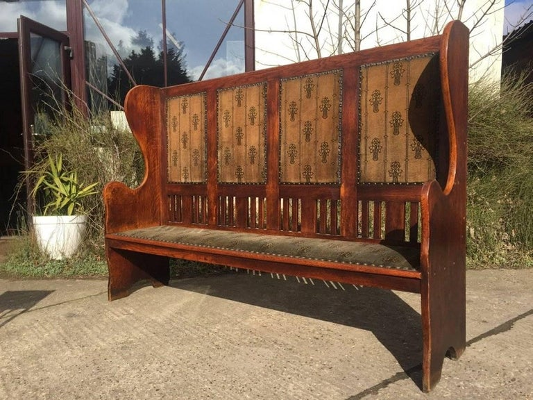 An Arts and Crafts Glasgow School oak settle in the style of M H Baillie Scott. Made by Wylie and Lochhead with sweeping curvaceous ends and a lower slatted detail, retaining it's original fabric with fantastic stylized Glasgow Roses which I must