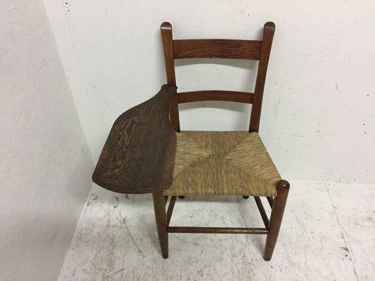 William Birch. An Arts and Crafts oak artist's sketching armchair with a shaped top for sketching or writing on. The shaped top supported on the upper leg with simple decorative hand-wrought iron work. Measure: The width is 23