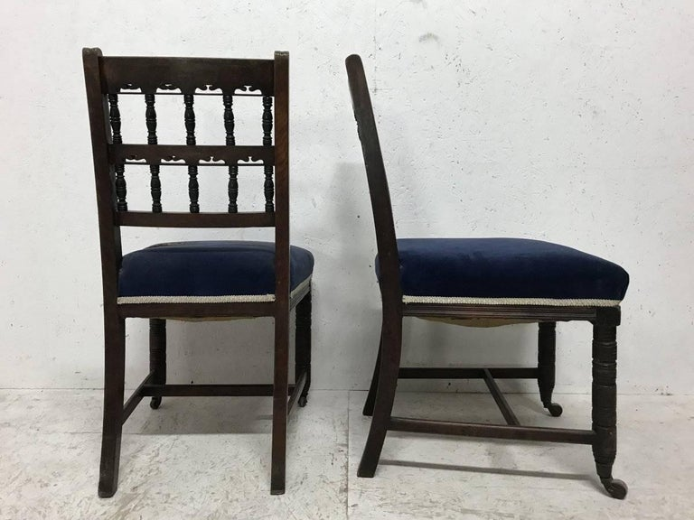 A good pair of Aesthetic movement walnut dining chairs designed by Bruce Talbert and probably made by Gillows of Lancaster. This pair has a nice contrast with ebonised spindles to the backrest. The chairs are also slightly larger all round and a bit