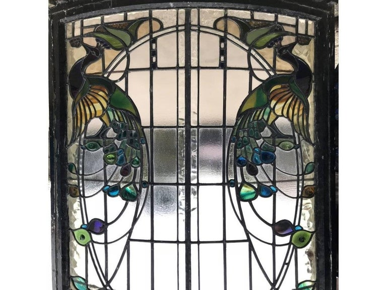 A rare and exceptional Arts and Crafts stained glass bow fronted window with colourful peacocks to each side, in it's original window frame with dentil mouldings to the top. The bottom was somewhat rotten but I have had a new piece of wood made as