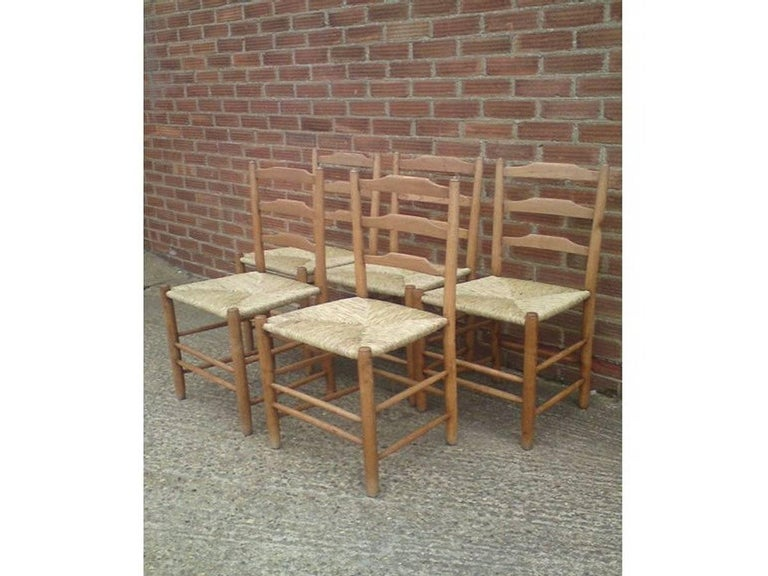 Edward Gardiner. A set of five Arts and Crafts Cotswold School ladder back dining chairs, with newly laid rush seats. These ladder back chairs are steeped in history, their design have evolved from a long line of English chair makers going back to
