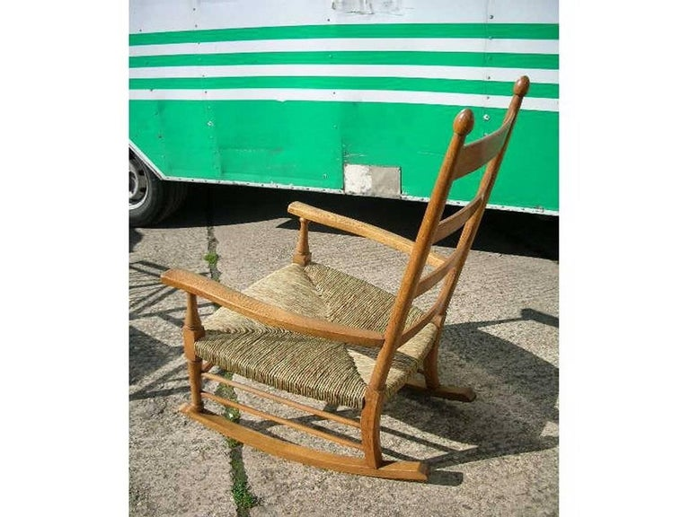 William Birch. An Arts and Crafts light oak ladder back rocking chair with turned finials, twin side stretchers.  A newly laid rush seat.
