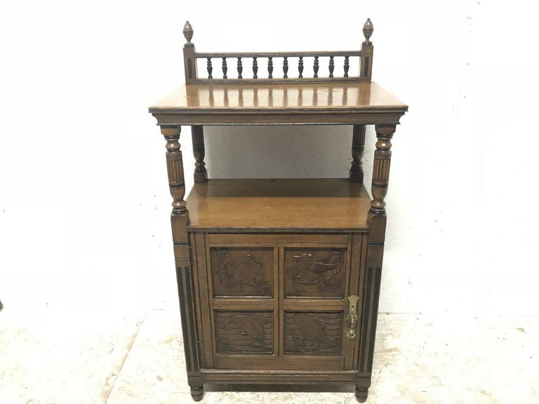 Charles Bevan for Gillows & Co. An Aesthetic Movement oak Canterbury, music or side cabinet with four carved panels, the upper pair depicting birds at dinner time, beaks full. The bottom pair with carved fish with young on a carved water effect back