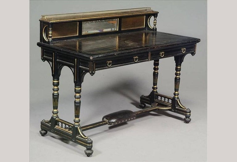 Bruce Talbert attr, made by Gillows and Co of Lancaster. Aesthetic Movement ebonised and parcel gilt desk. The upper shelf surmounted by a brass gallery, with a small central bevelled mirror and a black leather writing area with gilt tooling to the