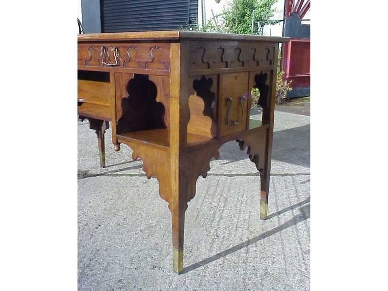 Edward William Godwin (1833-1886) for William Watt, an Anglo-Japanese walnut desk, with a leather inset top, blind fret frieze and on upper drawer fronts with long deep ledger drawers to the sides, shaped brackets, tapering legs with brass feet.