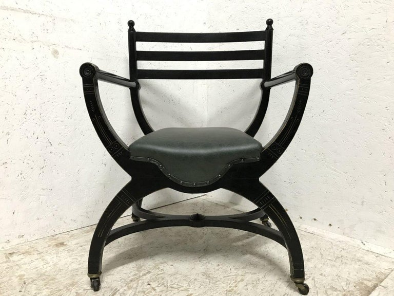 Richard Charles (1823-93), an Aesthetic Movement ebonized elbow chair, circa 1866, with ball finials, a ladder back, later leather seat, gilt highlights and X-frame base with X-frame stretcher, on casters, 83cm high. The attribution is based on the