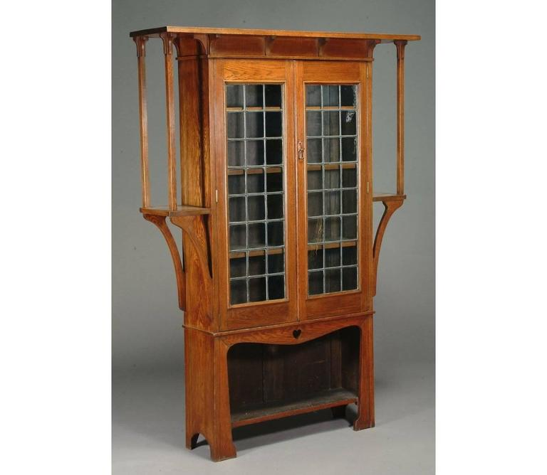 A near pair of oak Arts & Crafts bookcases by Liberty and Co. with two leaded glazed doors with adjustable shelves behind, with a single heart cut-out just above the lower open shelf. Extended shelves to each side with elongated supports uniting the