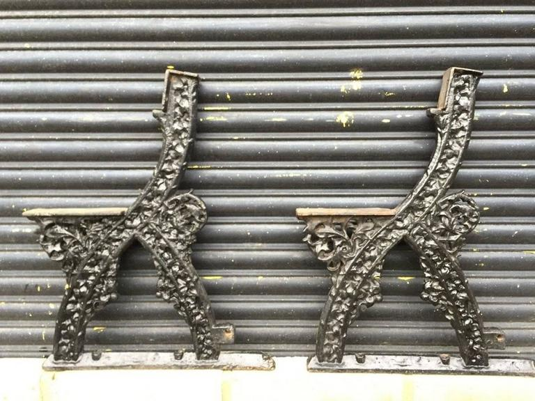 A rare pair of early Gothic Revival cast iron garden bench ends designed by A.W.N. Pugin with foliate details which is slightly obscured at the moment due to the many coats of paint. The first image here is to show how it can look when seating slats
