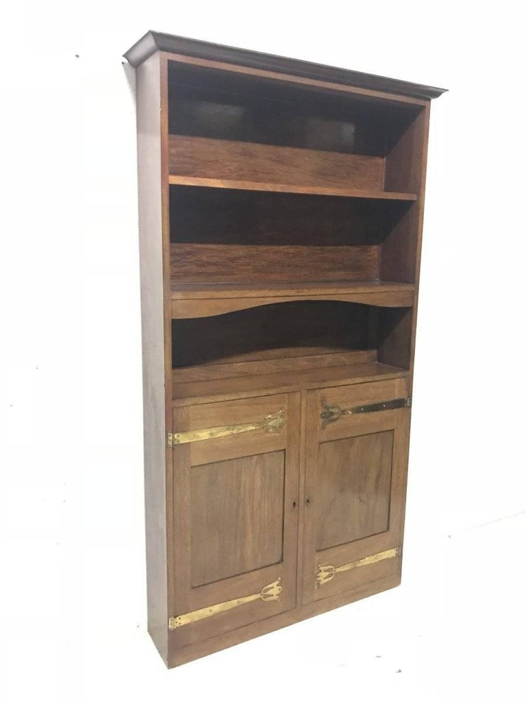 Liberty & Co. A Slim Arts & Crafts walnut bookcase with open upper shelves and cupboards below with stylised brass hinges.
