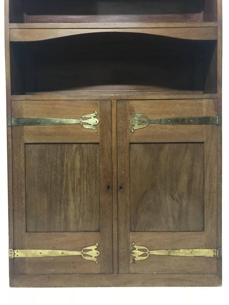 Liberty & Co. A Slim Arts & Crafts Walnut Bookcase with Stylised Copper Hinges In Good Condition For Sale In London, GB